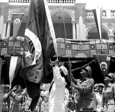 Egyptian President Gamal Abdel Nasser raises the Egyptian flag over the local naval headquarters at Port Said in celebration of the British military withdrawal from the canal zone a few days prior - Wikimedia Commons